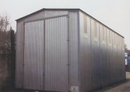 Sectional steel building with hinged doors